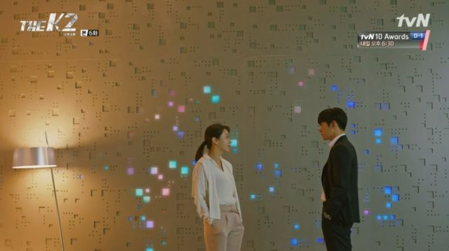 Yoo-jin and Je-ha in front of a fancy wall