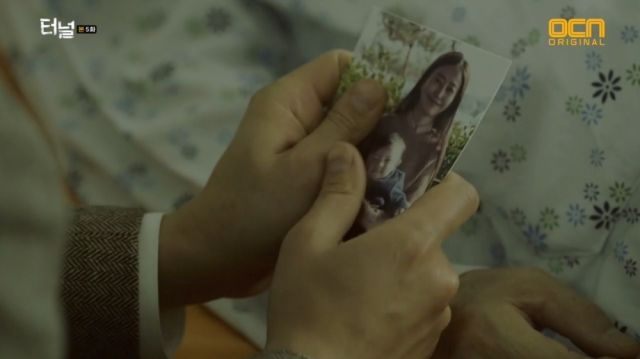 Seon-jae holding a picture of him and his mom